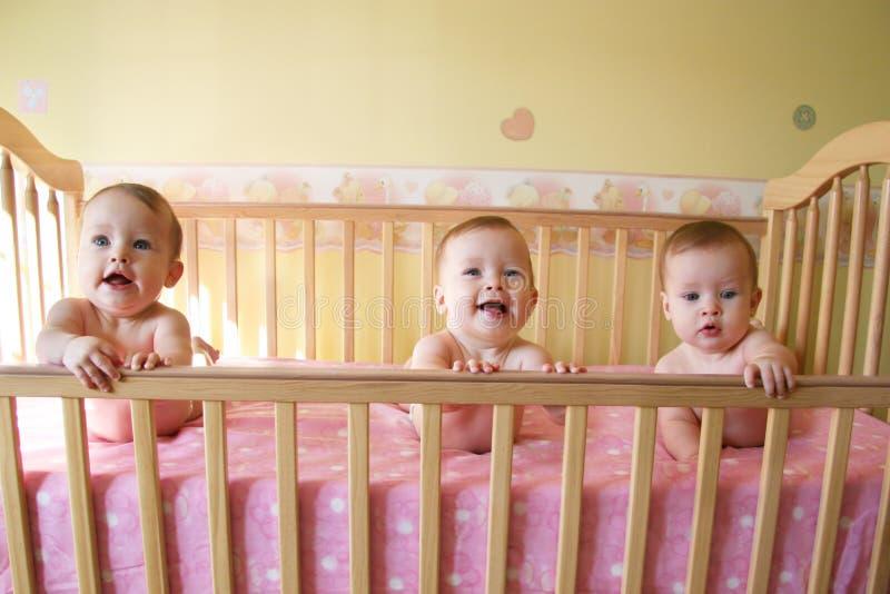 婴孩小儿床女孩三胞胎 免版税库存照片