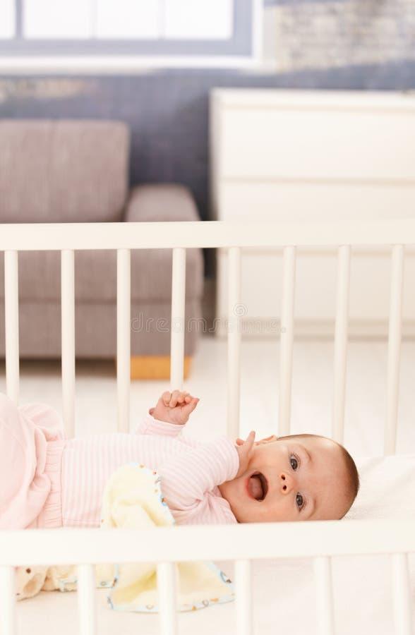 婴孩小儿床逗人喜爱的女孩 免版税库存照片