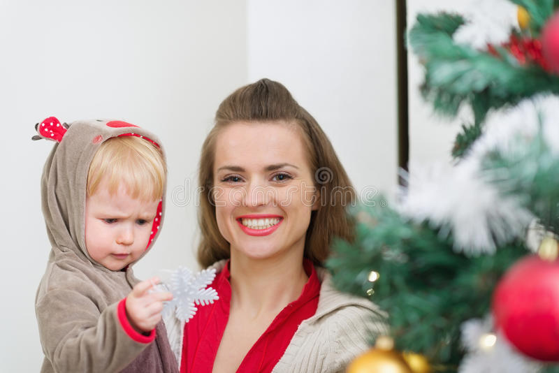 婴孩帮助的母亲装饰圣诞树 免版税图库摄影