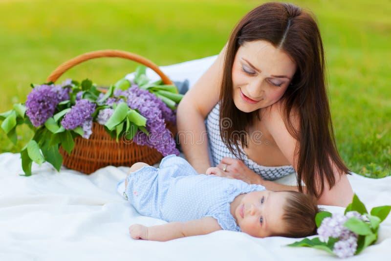 婴孩愉快的母亲公园休息的夏天 图库摄影