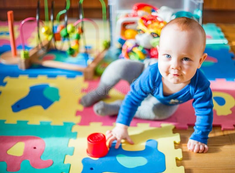 婴孩戏剧在他的屋子,许多玩具里 免版税库存照片
