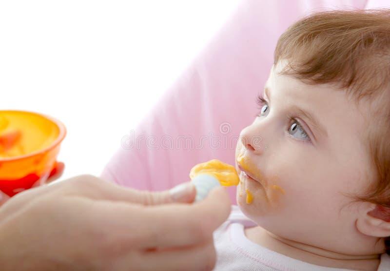 婴孩提供的母亲匙子黄色 库存图片