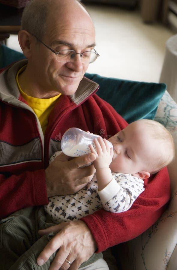 婴孩提供的祖父 库存照片