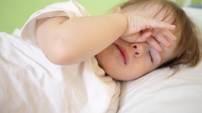 婴孩摩擦他的眼睛和尝试睡觉 小孩子睡着在他的小儿床 库存照片