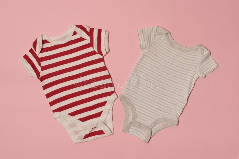 婴孩时尚在桃红色背景的衣裳概念 镶边和白色紧身衣裤 库存照片