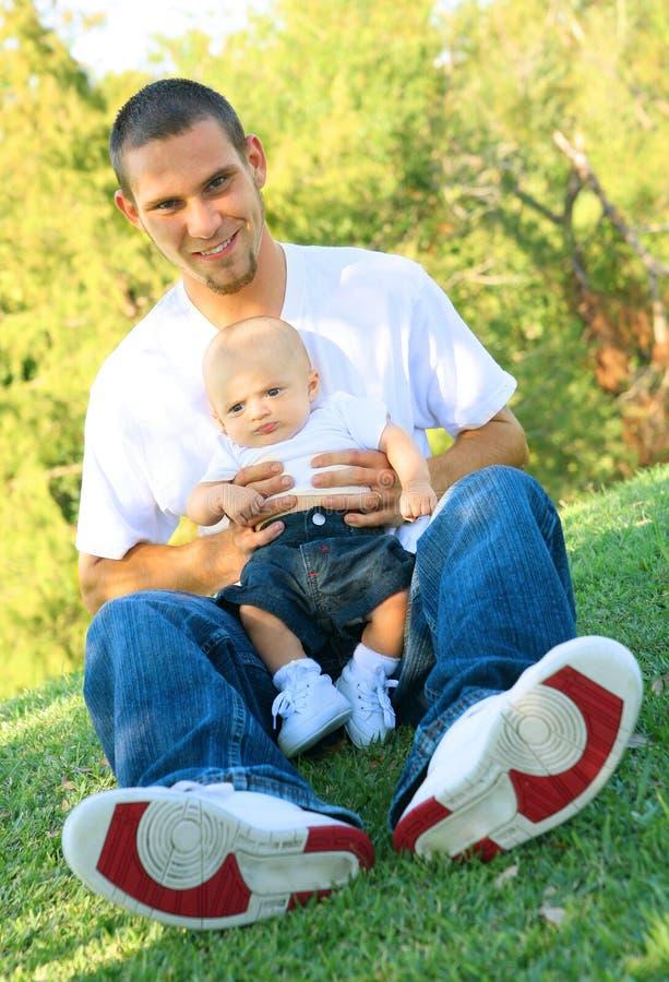 婴孩明亮的父亲暂挂室外公园年轻人 库存图片