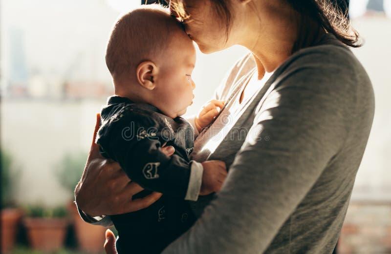 婴孩是完全地愉快的听到她i,如果亲吻母亲的图象感谢使用会您的地方 图库摄影