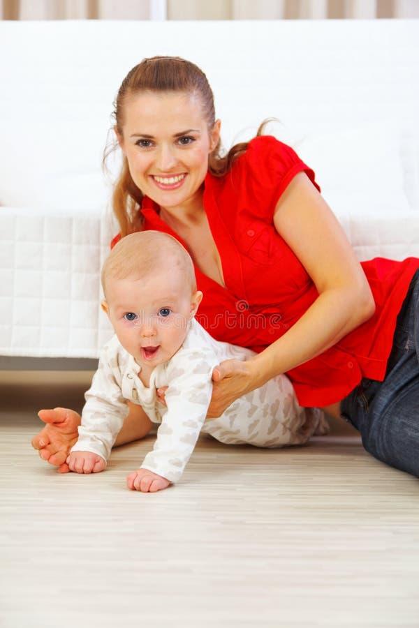婴孩楼层愉快可爱母亲使用 免版税库存照片