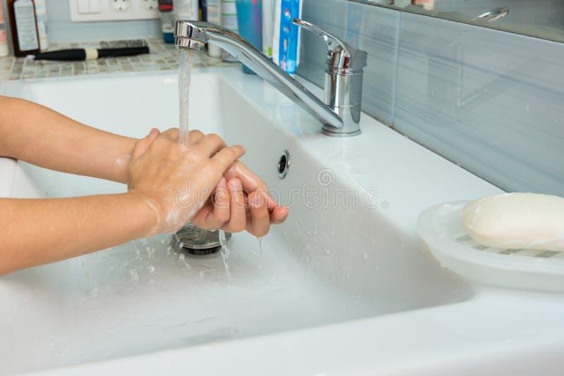 婴孩洗涤从手的肥皂在水盆 图库摄影