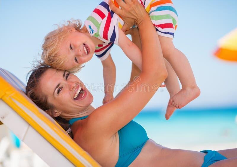 婴孩演奏纵向的海滩母亲 库存照片