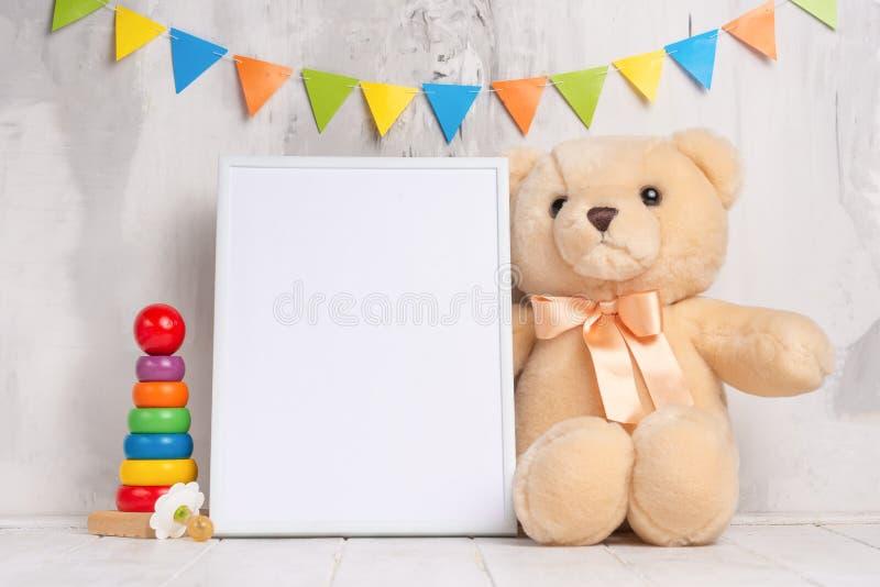 婴孩玩具和框架在轻的墙壁背景,设计的 婴孩出生的男孩看板卡新的阵雨 库存照片