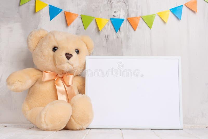 婴孩玩具和框架在轻的墙壁背景,设计的 婴孩出生的男孩看板卡新的阵雨 库存图片