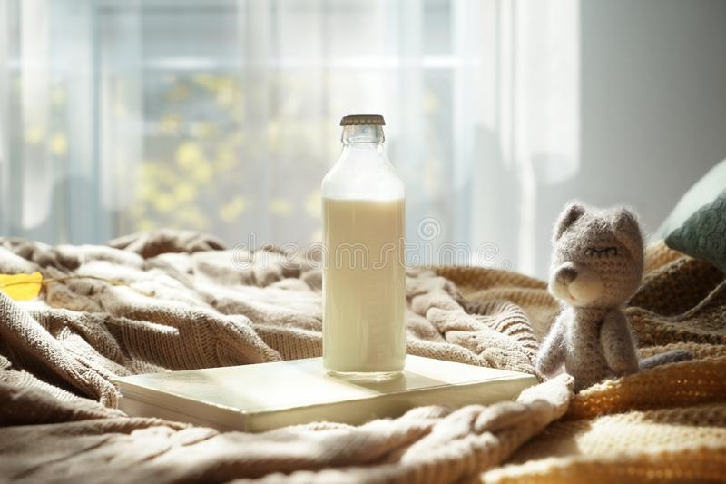 婴孩玩具和瓶在户内温暖的格子花呢披肩的牛奶 免版税库存图片