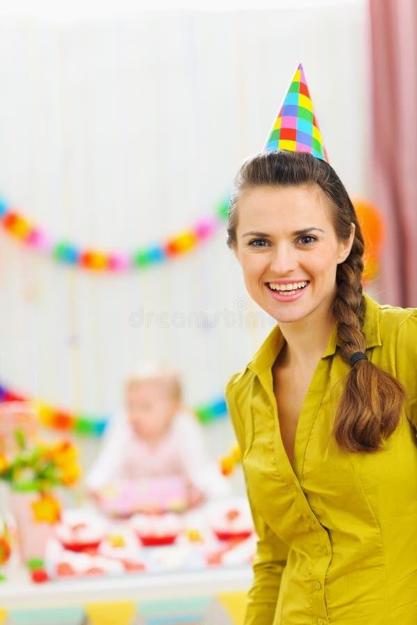 婴孩生日妈妈当事人纵向微笑 免版税库存照片