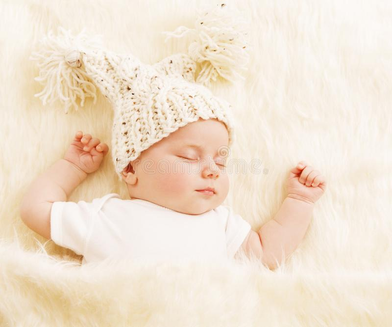 婴孩睡眠,在羊毛帽子的新出生的孩子睡觉在白色毯子的 库存图片