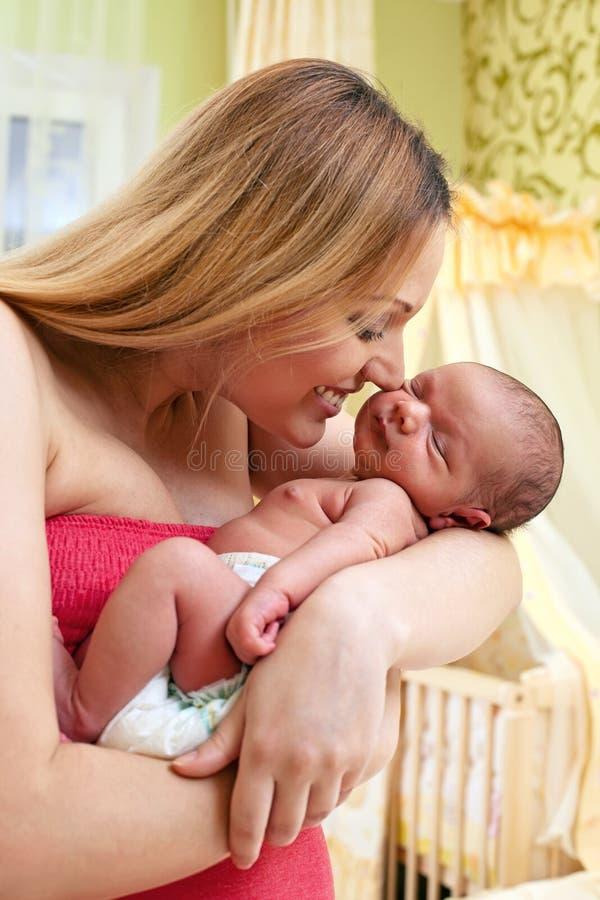 婴孩美丽的母亲新出生的年轻人 免版税库存图片