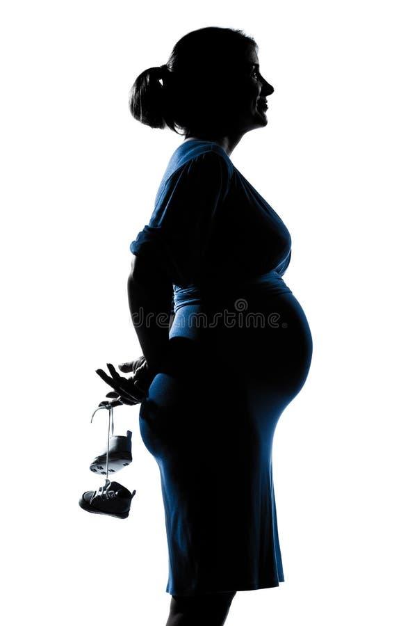 婴孩藏品纵向怀孕的鞋子妇女 库存图片