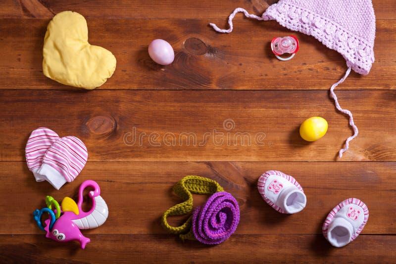 婴孩衣裳集合、被编织的棉花衣物、孩子玩具和辅助部件在棕色木背景,儿童新出生的时尚布料为 免版税库存图片