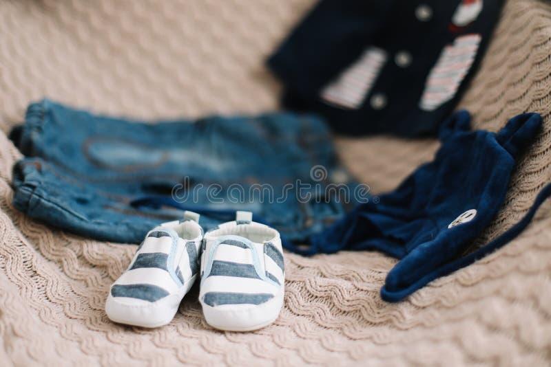 婴孩衣裳顶视图时尚时髦神色,时尚概念 一个对男婴鞋子 免版税库存照片