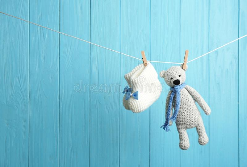 婴孩赃物和玩具涉及洗衣店线反对颜色木背景 儿童辅助部件 库存图片