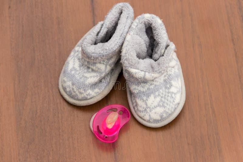 婴孩赃物和soother在木背景 库存图片