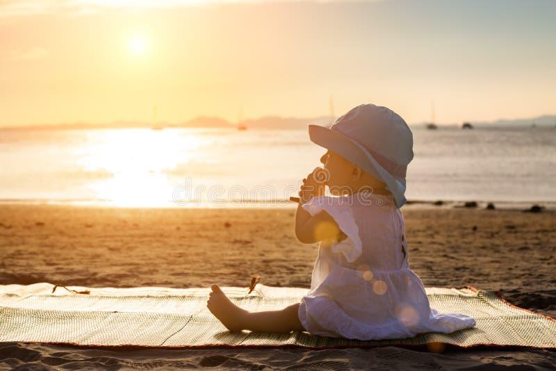 婴孩长牙齿 一切咬,嚼 坐热带沙滩和寻找日落的婴儿女孩 免版税库存照片