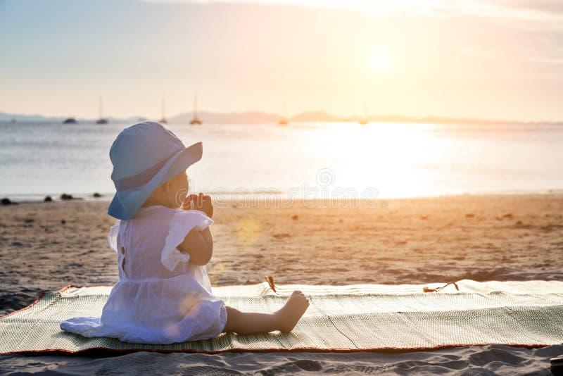 婴孩长牙齿 一切咬,嚼 坐热带沙滩和寻找日落的婴儿女孩 免版税库存图片