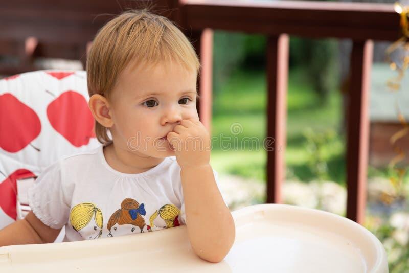 婴孩高脚椅子开会 选址在空的桌上的女孩和等待您哺养 免版税库存照片