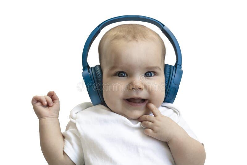 婴孩,孩子,小孩愉快微笑在白色背景的无线蓝色耳机 学会从的技术的概念 免版税图库摄影