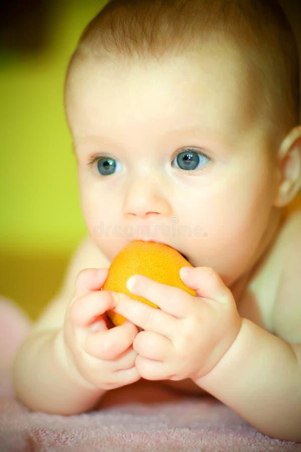 婴孩eates蜜桔 库存照片