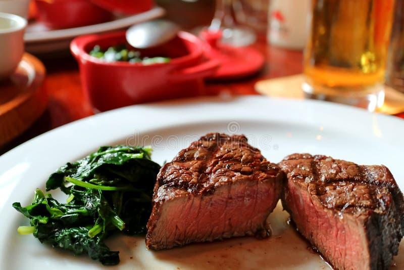 媒介烤了里脊肉牛排切成了两半用在白色板材的嫩煎的菠菜 免版税库存照片