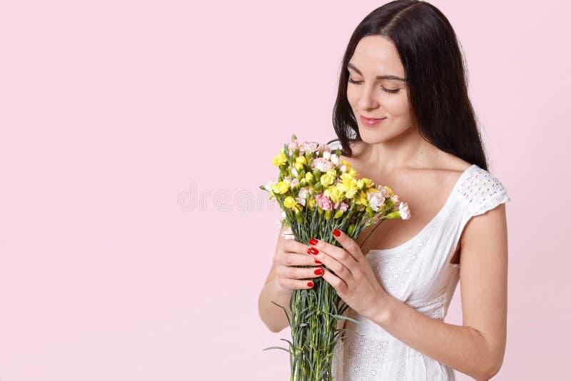 嫩可爱的年轻女人画象有长的黑色头发的在夏天白色礼服藏品花束,嗅到的花,被隔绝 免版税库存照片