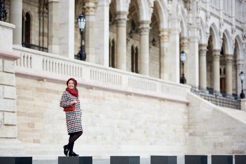 嫩女性微笑的站立反对城市建筑学在布达佩斯 免版税库存图片