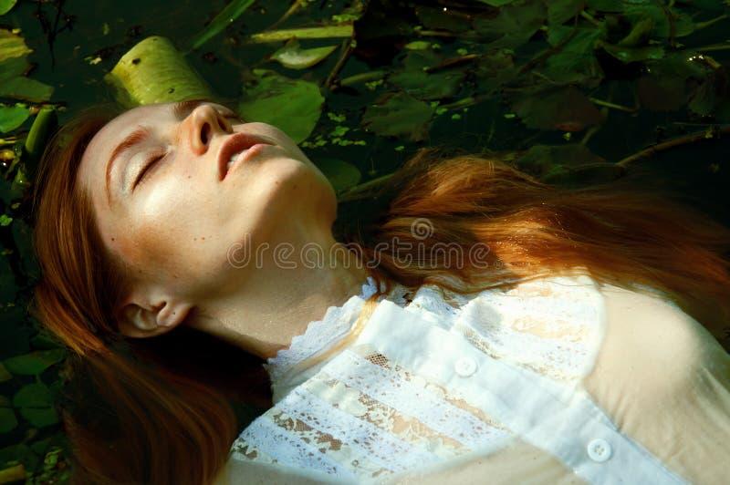 嫩少妇游泳在荷花中的池塘 免版税图库摄影