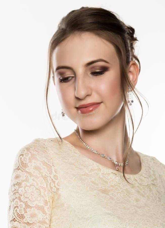 嫩少妇画象奶油色礼服的在白色背景 应用光泽嘴唇组成专业人员 库存图片