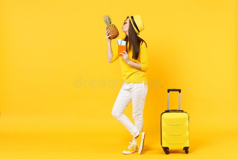 嫩帽子藏品护照票的旅客旅游妇女,亲吻在橙黄隔绝的菠萝果子 免版税图库摄影