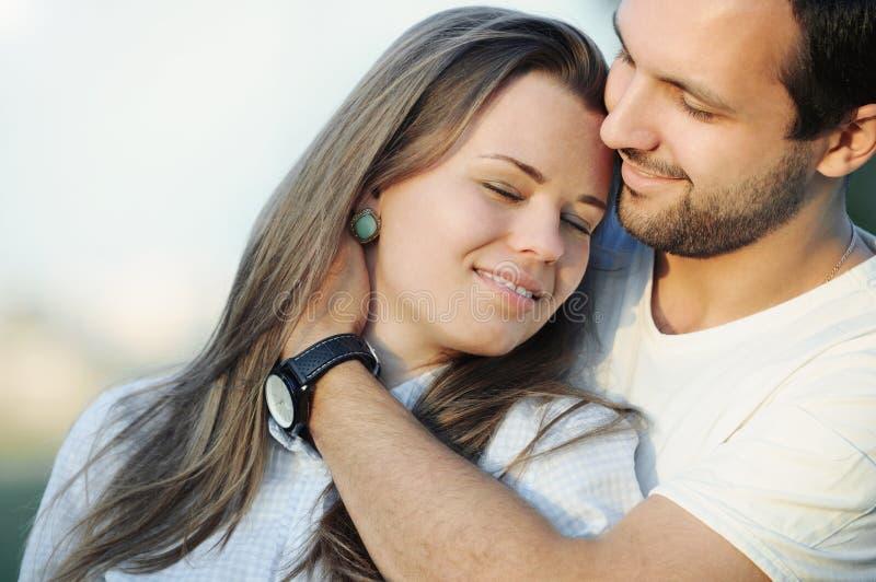 嫩肉欲的年轻夫妇画象在摆在日落的爱的 库存图片