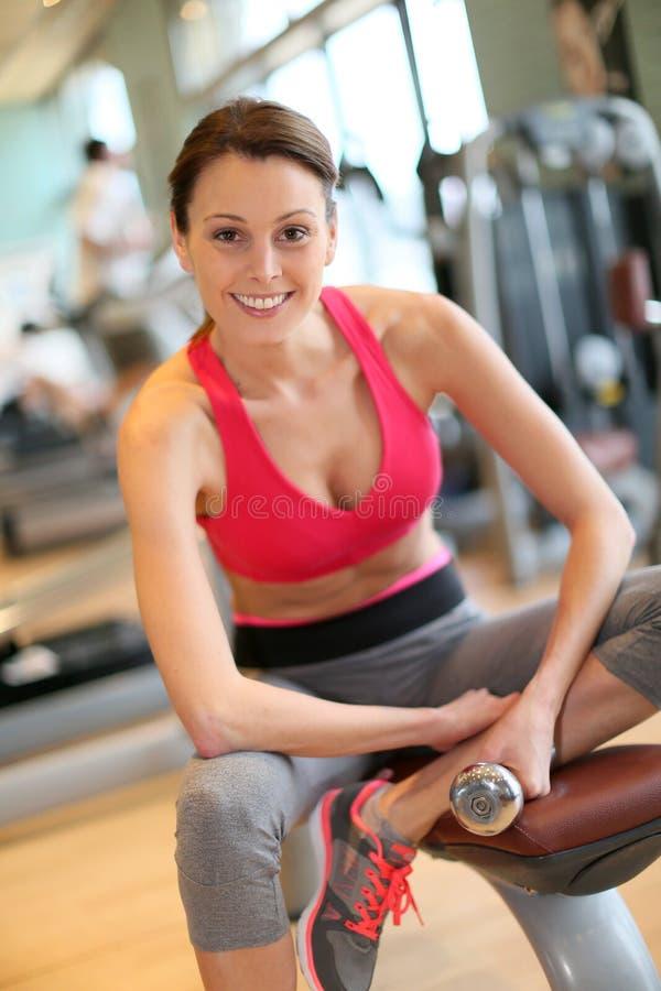 嬉戏少妇举的重量在健身中心 免版税图库摄影