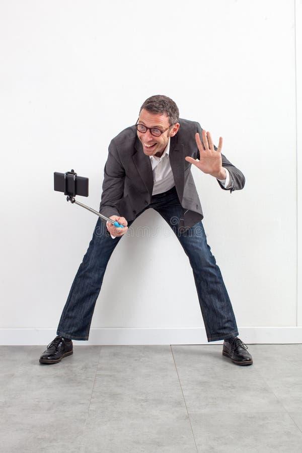 嬉戏的中部年迈的商人问好在selfie 免版税图库摄影