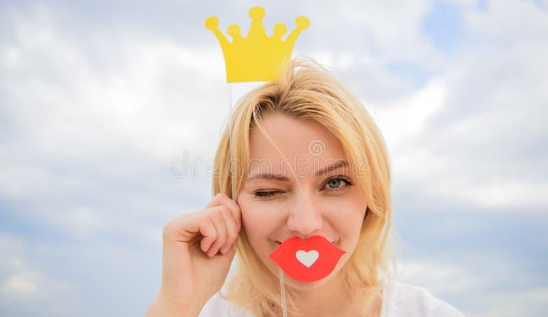 嬉戏的公主 妇女金发举行纸板冠状头饰或冠和爱天空背景的红色嘴唇标志 夫人 库存图片