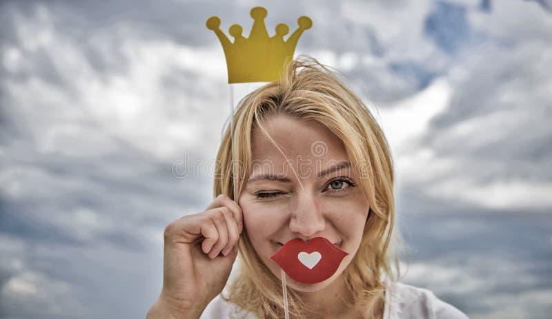 嬉戏的公主 妇女金发举行纸板冠状头饰或冠和爱天空背景的红色嘴唇标志 ?? 免版税库存照片
