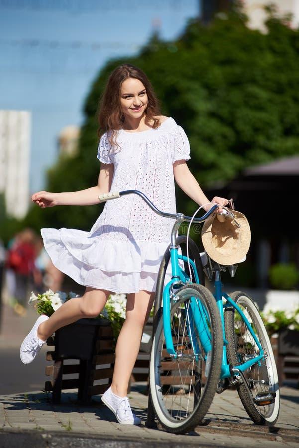 嬉戏的女孩在与减速火箭的自行车的阳光下在城市街道上 免版税库存照片