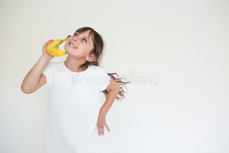 嬉戏的女孩用香蕉果子 库存照片
