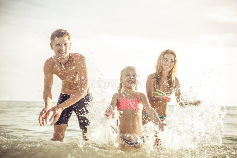 嬉戏的家庭喷洒的水和有乐趣 库存图片