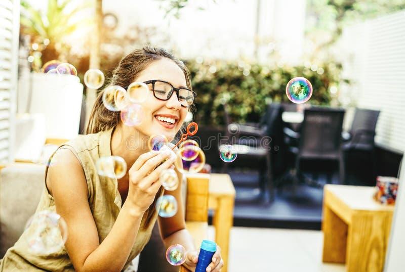 嬉戏的年轻女人吹的党泡影肥皂-飘渺在后院-幸福,喜悦,女孩幼稚概念 库存照片