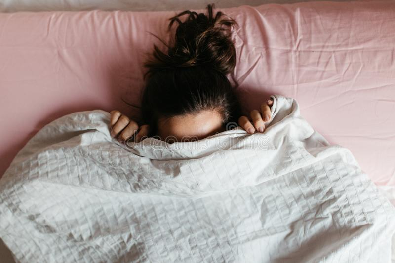 嬉戏的年轻女人,在毯子下面躲脸,躺在白色枕头上舒适的床上,好奇的女孩,害羞地偷窥 免版税库存图片