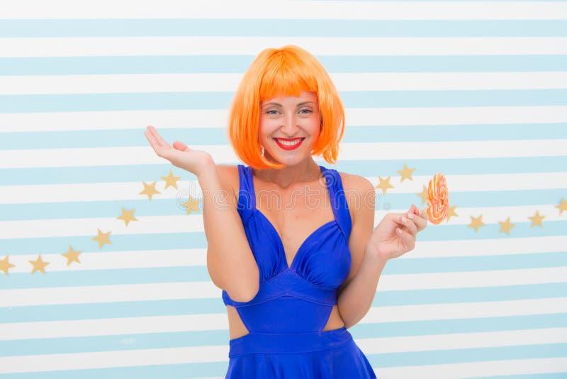 嬉戏的心情的疯狂的女孩 有棒棒糖的凉快的女孩 性感的妇女 有获得橙色的头发的时尚女孩乐趣 愉快的画报 图库摄影