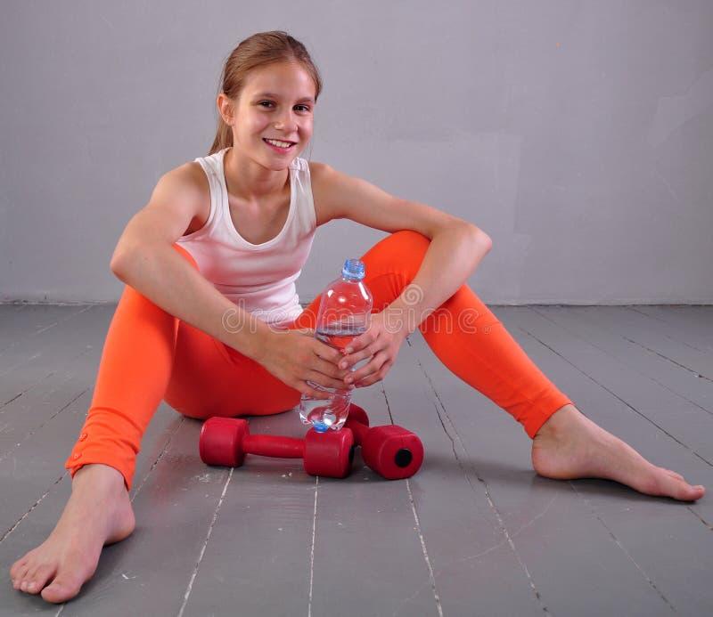 年轻嬉戏青少年的女孩画象有一个瓶的饮用水 免版税库存图片