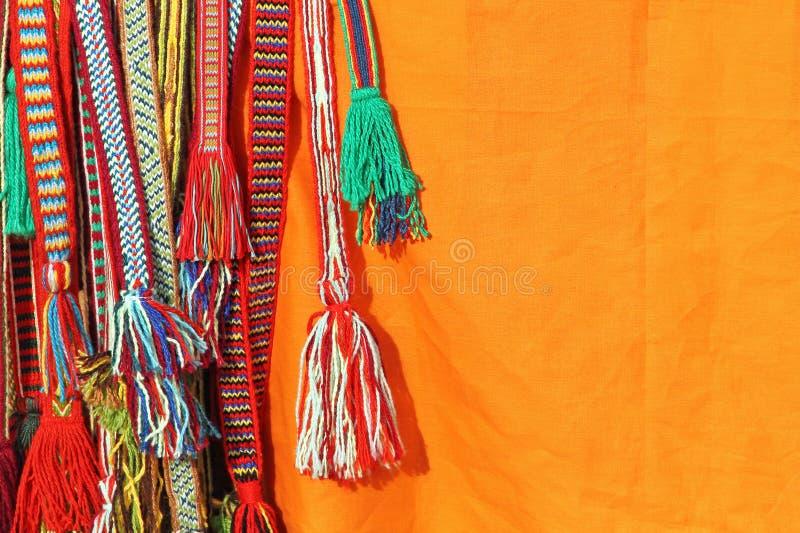 嬉皮传送带的五颜六色的缨子在橙色背景的 库存照片