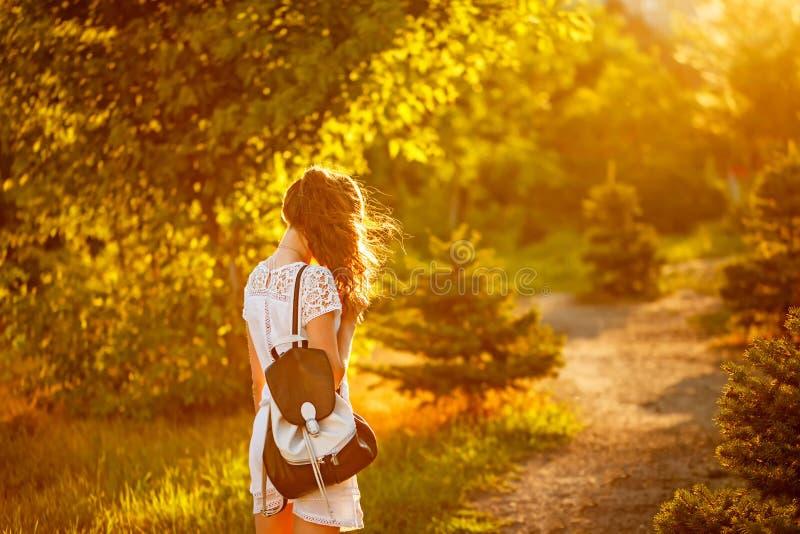 嬉皮女孩步行在公园 照片从后面 免版税库存图片